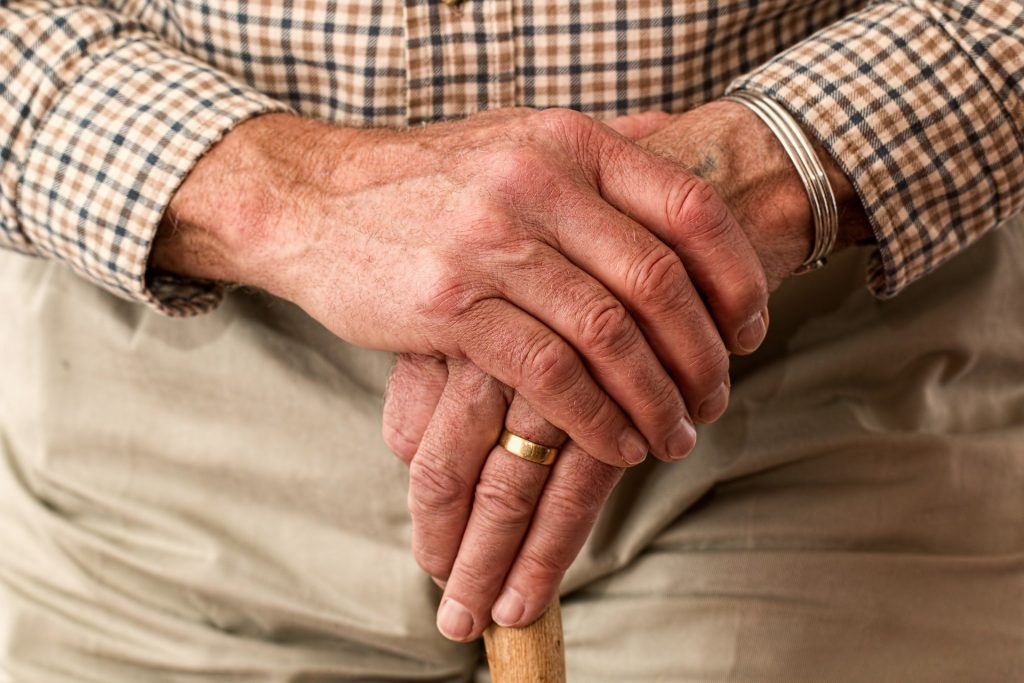 an elderly mans hands resting on a walking stick symbolising a need for companionship