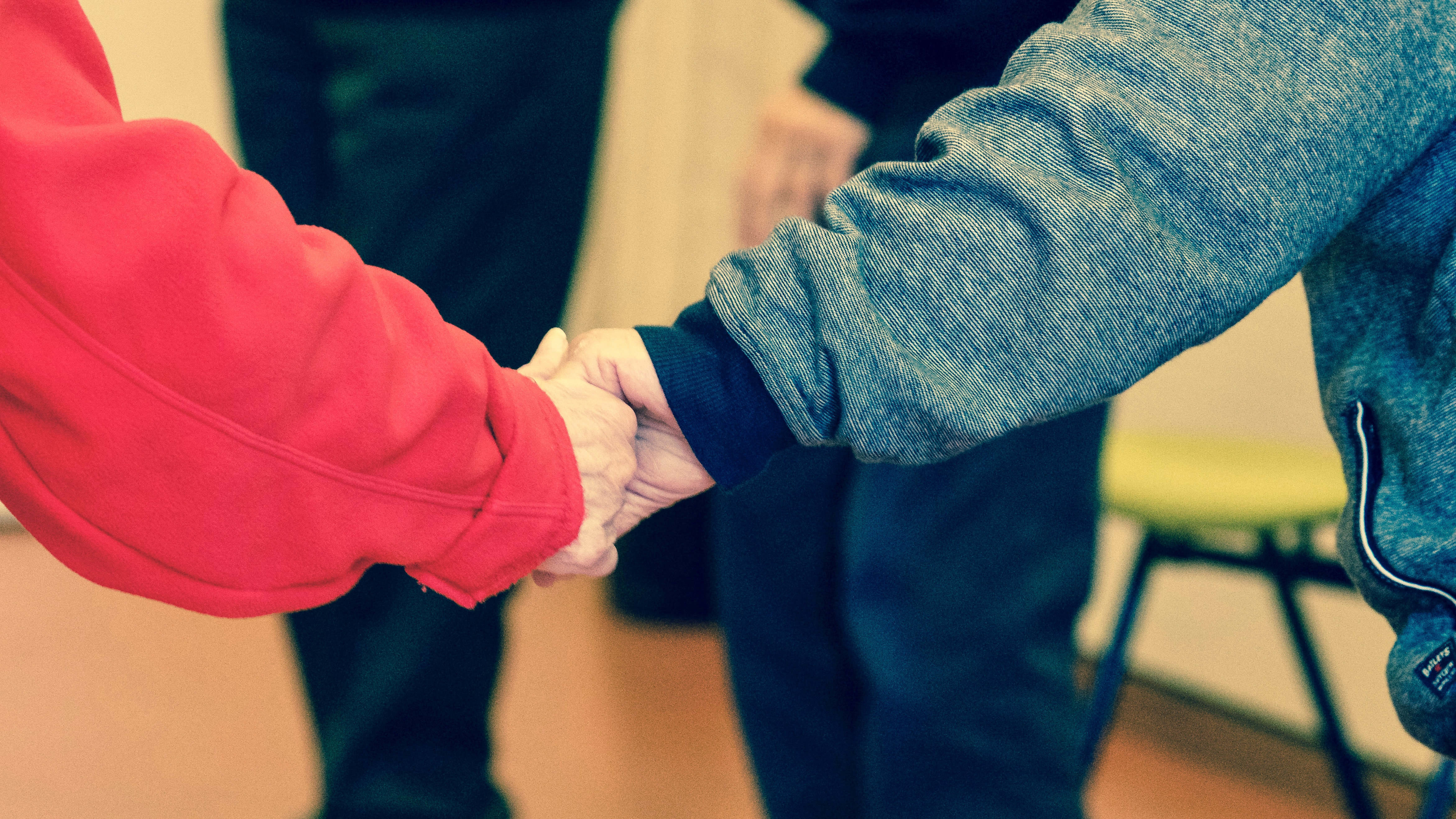 Someone living with dementia holding hands with a carer