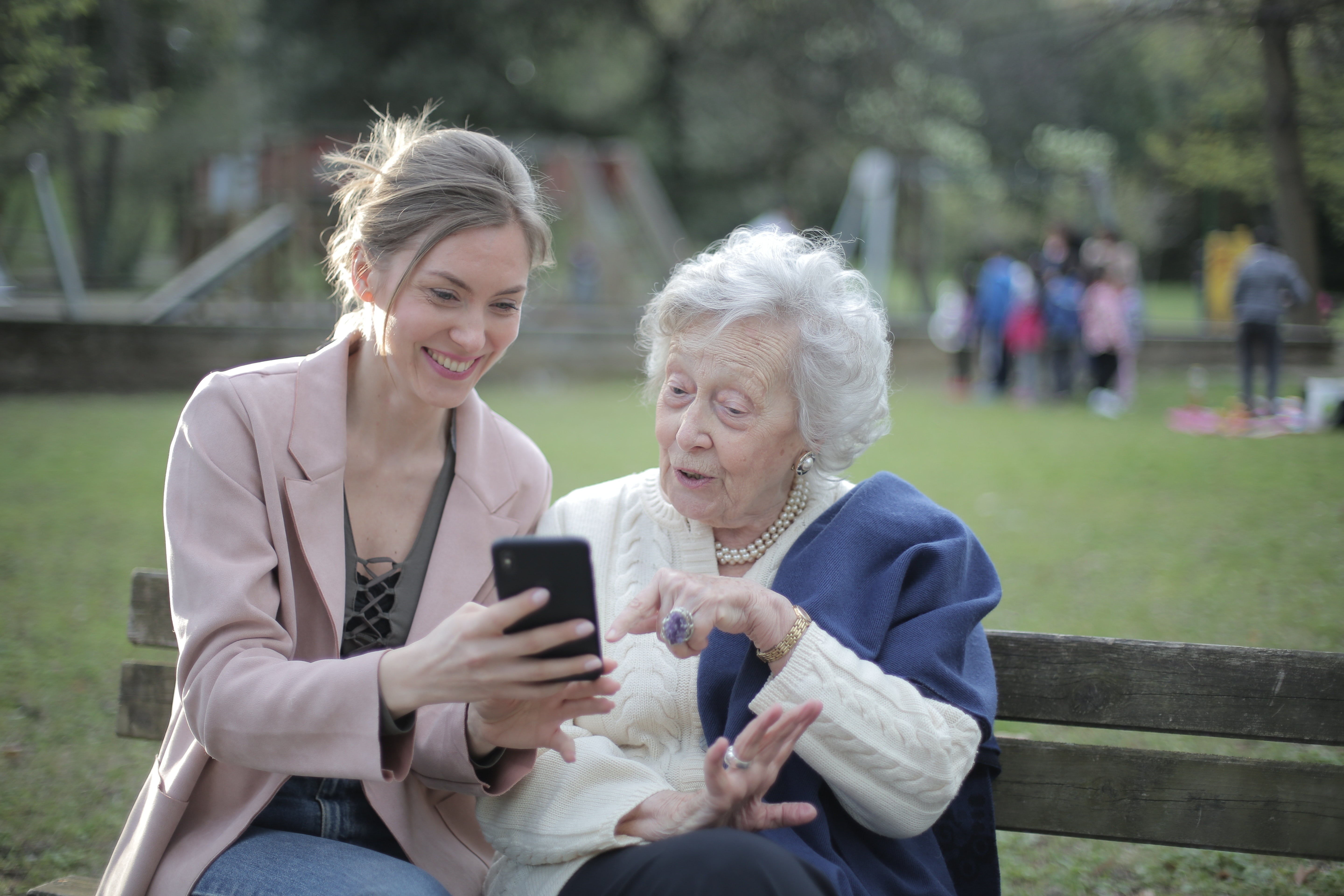 A younger woman showing an older woman something on a phone